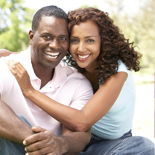 A couple embracing and smiling because of the restorative dental services available at this dentist in Savannah GA- Restore, complete, and renew your moments of joy