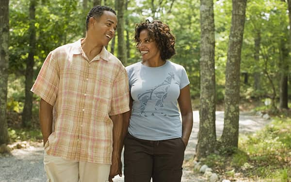 A middle aged couple smiling and walking with CEREC dental crowns.